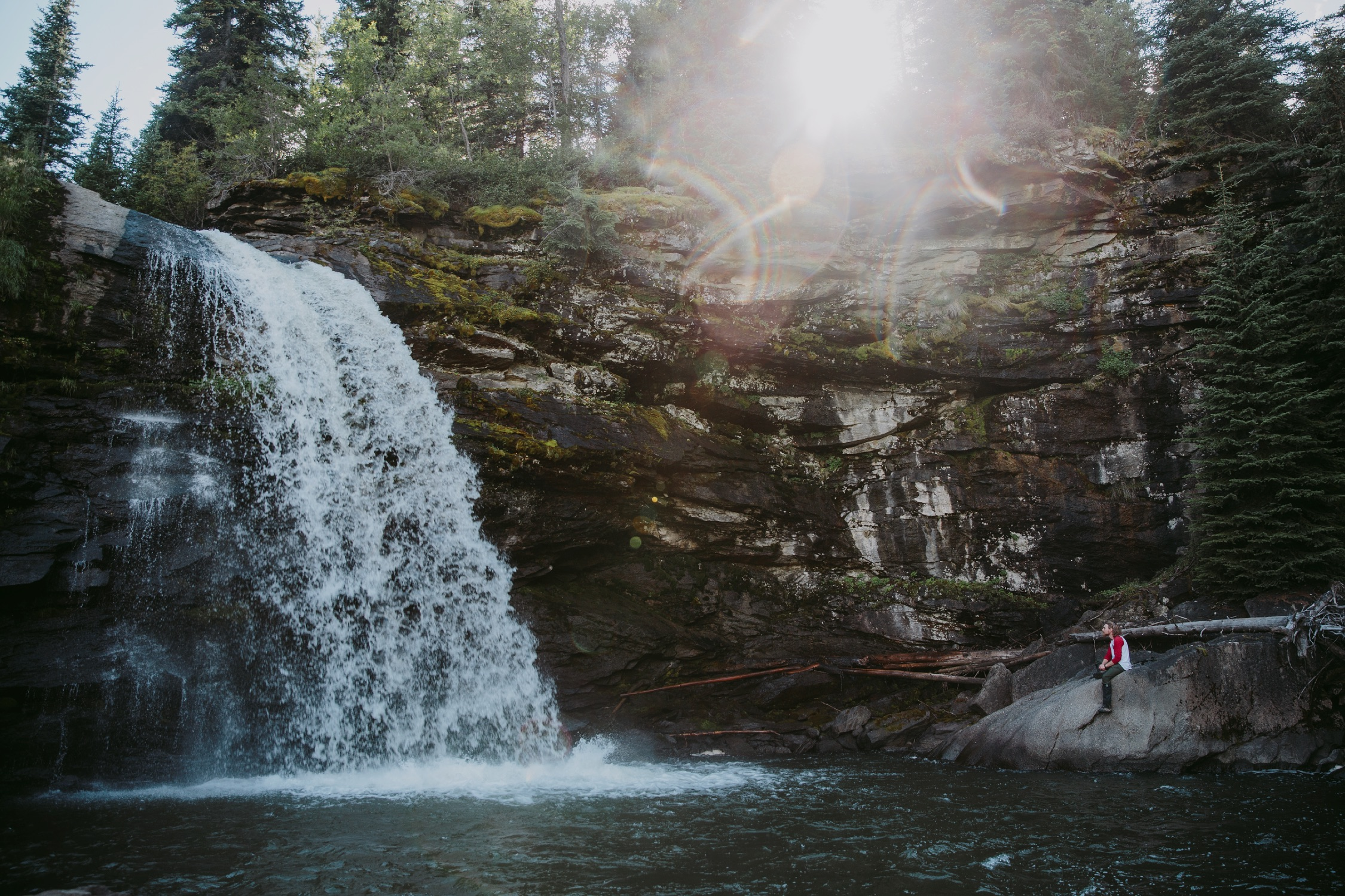 A person sits on a rock next to Babcock Falls in Tumbler Ridge.