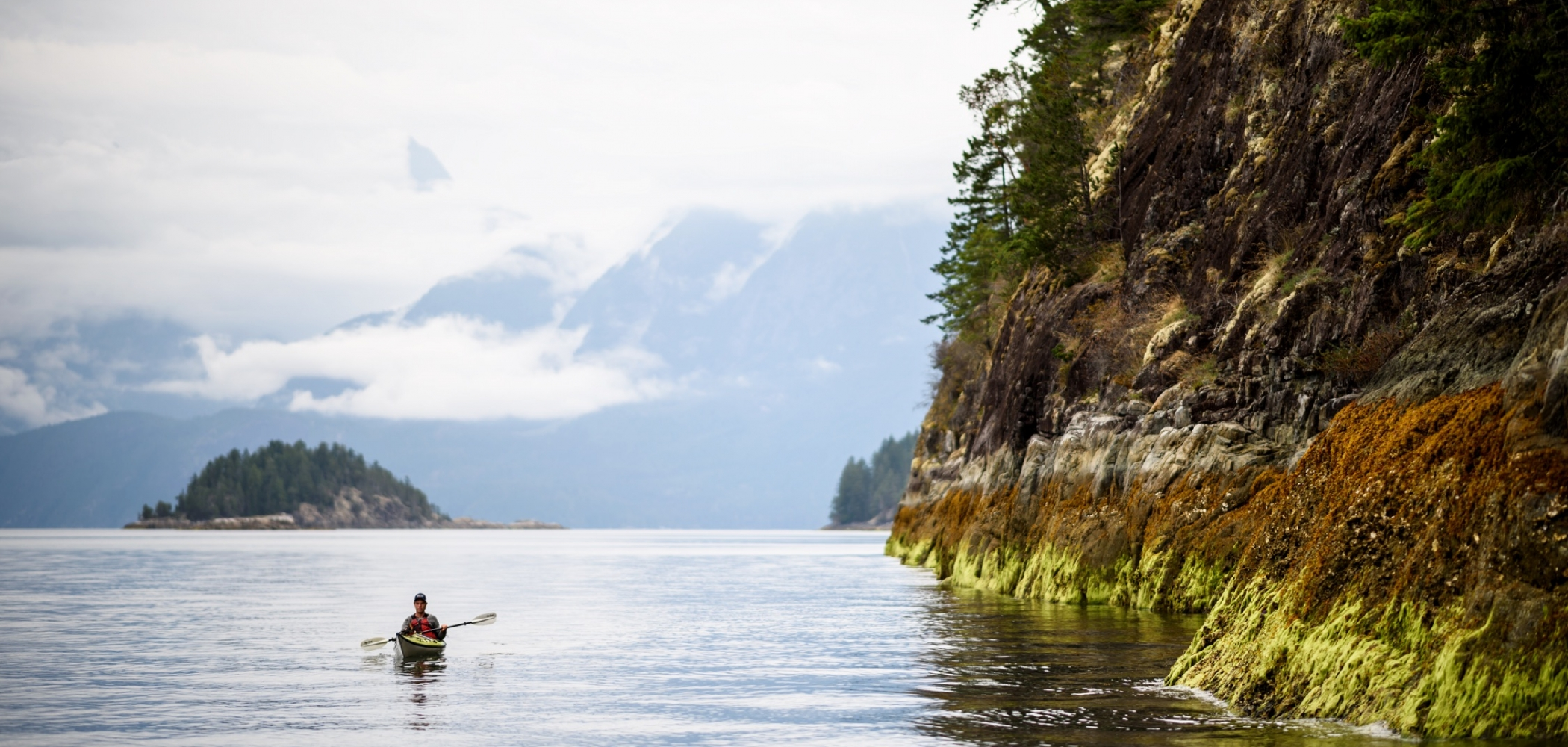A kayaker paddles along the rugged coastline of Desolation Sound at low tide.