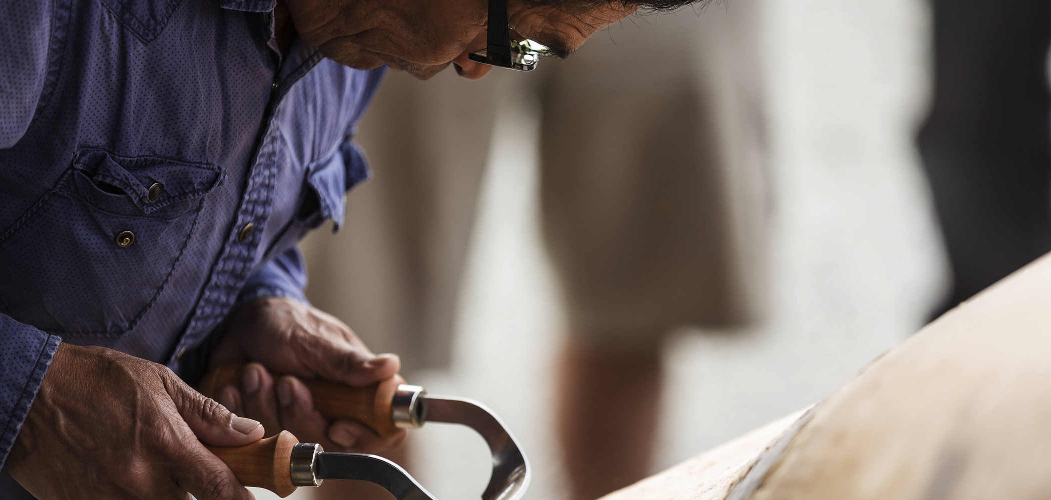 A first nations carver working on a dugout canoe checks his work while using an Inshave carving tool . Tofino, Vancouver Island, British Columbia, Canada.